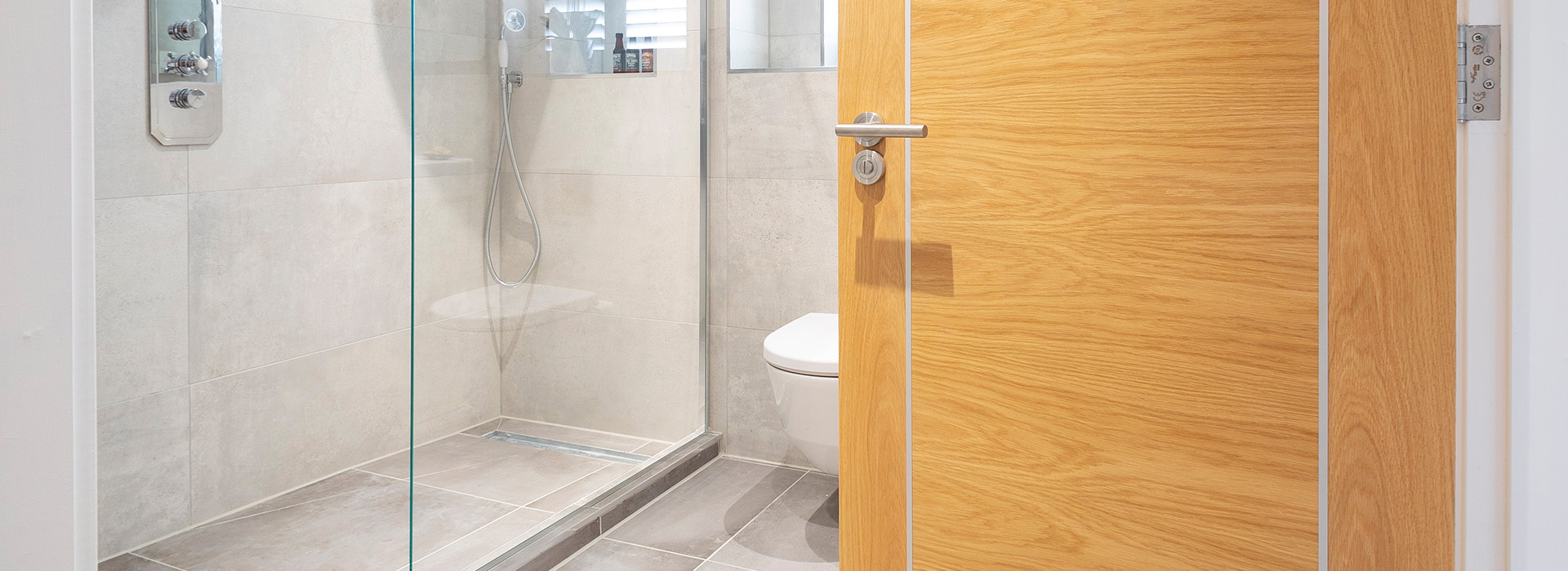 Grey bathroom tiles and oak doors